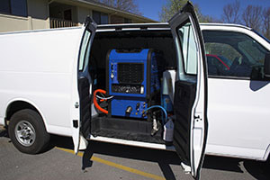 van with side doors open showing cleaning equipment for carpet, tile grout, and upholstery